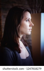 portrait of brunette young woman looking out of window
