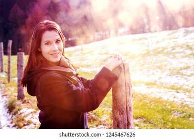 portrait of brunette young woman standing outdoors at snowy fields in the sun