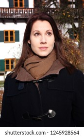 portrait of brunette young woman standing outdoors in front of bavarian house in the cold
