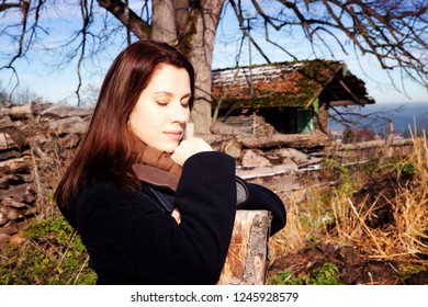 portrait of brunette young woman standing outdoors and resting