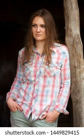 portrait of brunette young woman standing outdoors at wooden pole