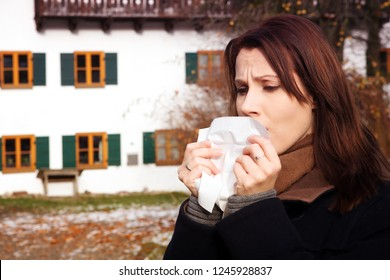 portrait of brunette young woman with tissue and having a cold outdoors