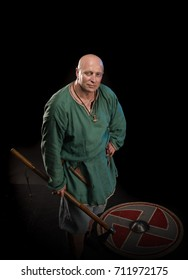 Portrait of a brutal bald Viking in linen clothes with a shield and hatchet in hands posing on a black background. Early medieval period.