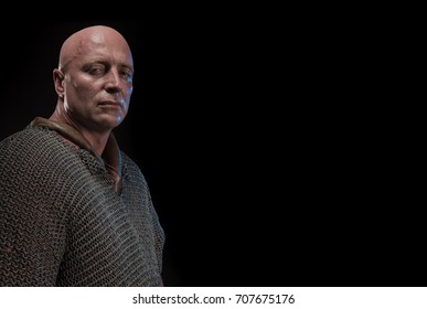 Portrait of a brutal bald-headed viking in a chain armor with a helmet in his hands posing against a black background. Early medieval period.