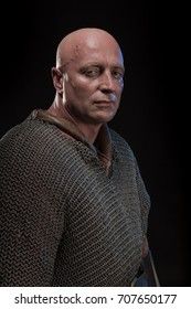 A portrait of a brutal bald-headed viking puts on or takes off the chain mail, posing against a black background. Early medieval period.