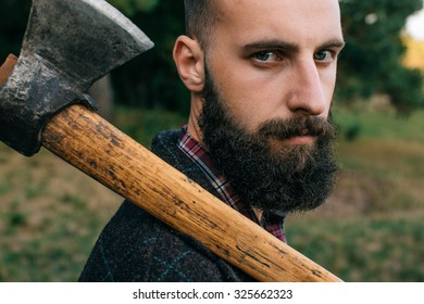 Portrait brutal bearded hipster man in the forest with ax