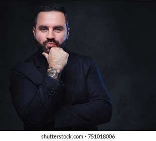 Portrait of brutal bearded macho male dressed in a suit over dark grey background.