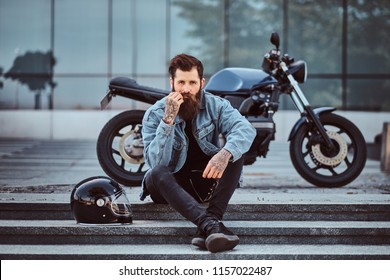 Portrait of a brutal bearded male dressed in a jeans jacket sitting on steps near his custom-made retro motorcycle against skyscraper.