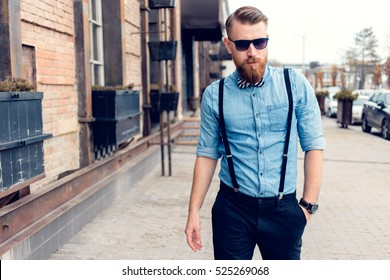 Portrait of a brutal bearded man walking in the street. Young stylish hipster posing, sunglasses, mustache, the bow tie, suspenders.  Businessman looking looking at the camera outdoors.