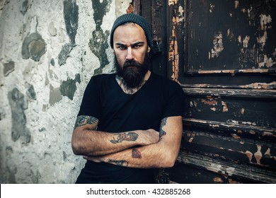 Portrait of brutal bearded man wearing blank t-shirt on the door