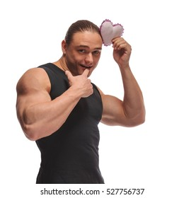 Portrait of a brutal man bodybuilder athlete with a soft toy heart in hands on a white background