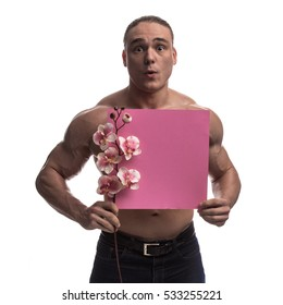 Portrait of a brutal man bodybuilder athlete with a sprig of blooming pink orchids and pink sheet of paper for notes in the hands on a white background