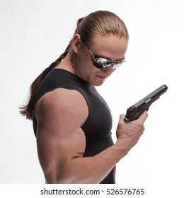 Portrait of a brutal man bodybuilder in sunglasses with a gun on a white background