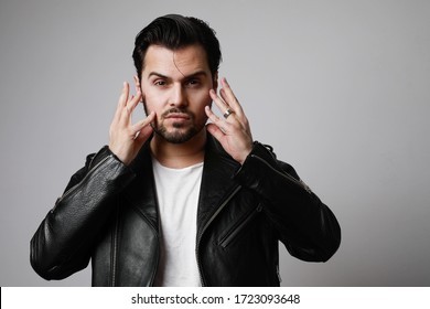 Portrait of brutal man with dark beard, looks aside, wears leather jacket, over blank studio background with free space.
