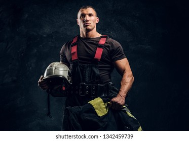 Portrait of a brutal muscular fireman holding a helmet and jacket standing in the studio against a dark textured wall
