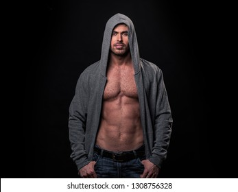 Portrait of brutal muscular man dressed in a grey hoodie isolated on black background