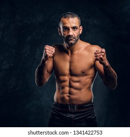 Portrait of a brutal professional fighter with naked torso posing for a camera. Studio photo against a dark textured wall