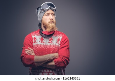 Portrait of a brutal redhead bearded male in a winter hat with protective glasses dressed in a red sweater, posing with crossed arms at a studio. Isolated on the gray background.