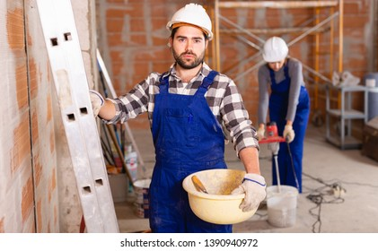 Portrait of builder in process of finishing work in cottage
