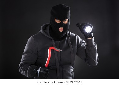 Portrait Of A Burglar Using Flashlight And Crowbar On Black Background