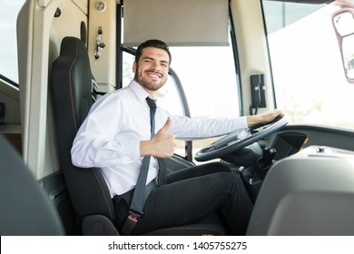 Portrait of bus driver showing thumbs up while sitting in travel bus