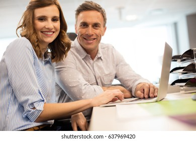 Portrait of business colleagues working together on laptop at desk in office