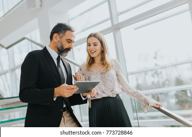 Portrait of business couple with digital tablet in office