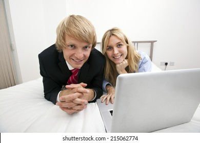 Portrait of business couple with laptop lying on bed