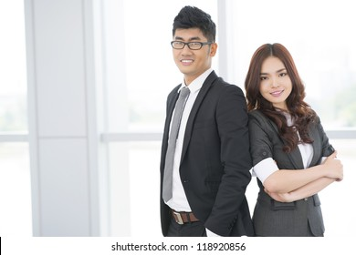 Portrait of business duo with ambitious look and confident smiles