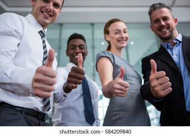 Portrait of business executive showing thumbs up in office