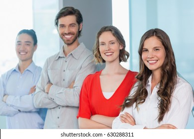 Portrait of business executives with arms crossed smiling while standing in office