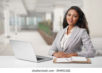 Portrait of business lady in headset consulting a client