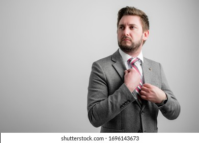 Portrait of business man arranging his business jacket isolated on grey background with copy space advertising area