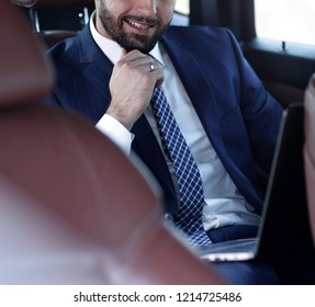 Portrait of a business man in the back seat of a car