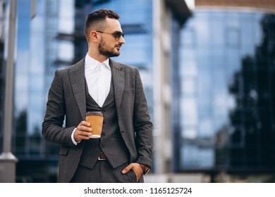 Portrait of business man by the skyscraper drinking coffee
