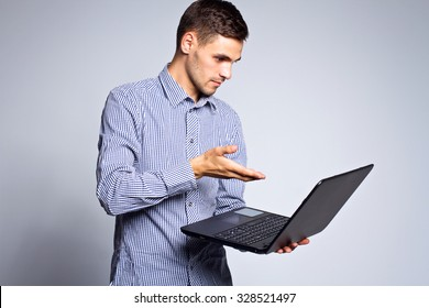 Portrait of business man with a laptop on a gray background