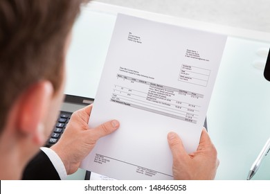 Portrait of a business man looking at invoice paper
