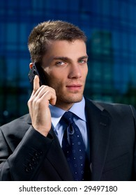 Portrait of business man outside the building using cell phone