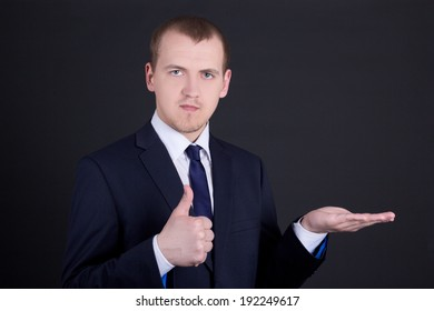 portrait of business man showing something on his hand and thumbs up