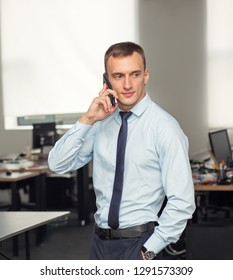 Portrait of a business man talking on a smartphone in the office. Sales by phone.
