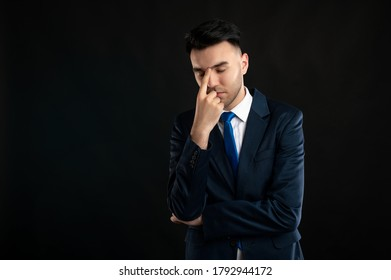 Portrait of business man wearing blue business suit and tie making thinking gesture isolated on black background with copy space advertising area