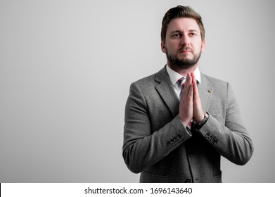 Portrait of business man wearing business clothes is praying isolated on grey background with copy space advertising area