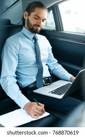 Portrait Of Business Man Working On Notebook, Traveling In Car. Confident Young Businessman Working On Laptop While Going To Work In Comfortable Transport. Business Trip. High Resolution.