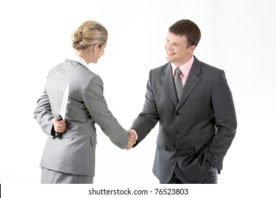 Portrait of business partners handshaking while female holding knife behind her back