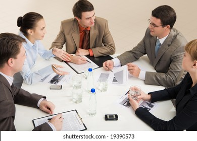 Portrait of business people sitting around table and interacting