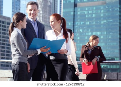 Portrait of business team outside office on skyscrapers background
