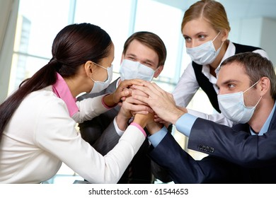 Portrait of business team in protective masks making pile of hands