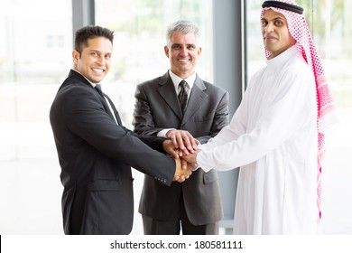 portrait of business team putting their hands on top of each other