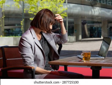 Portrait of a business woman adjusting her hair and looking at reflection on screen on laptop