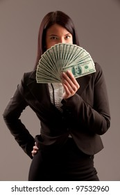portrait of business woman holding fan of money